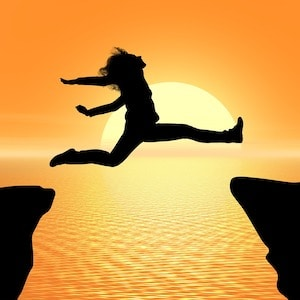 Woman jumping across a chasm to illustrate good planning